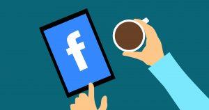 hombre tomando cafe viendo facebook en una tablet rentabilidad empresas