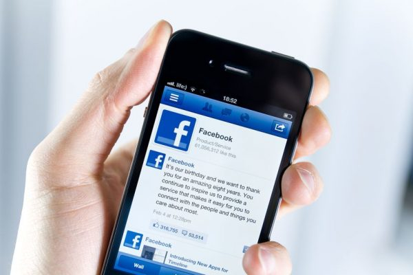 un hombre sosteniendo un movil apple iphone4 con la app de facebook