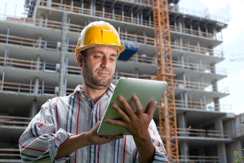 FOTO: Hombre en una construcción leyendo notificaciones de marketing en un ipad
