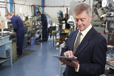 IMAGEN: Jefe de ingeniería con tablet y personal en el fondo - marketing de las Empresas Industriales