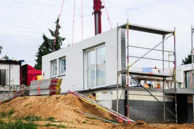 Foto de archivo - El montaje de una pared de la casa en una casa prefabricada.